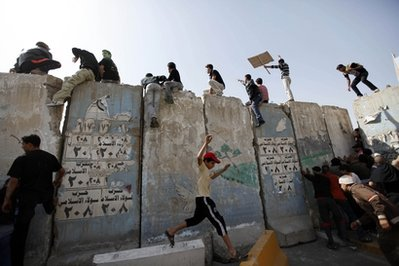 Iraqi_anti-government_protesters_climb_and_push_concrete_blast_walls_leading_to_the_heavily_guarded_Green_Zone_during_a_demonstration_in_Baghdad_IraqFriday_Feb_25_2011